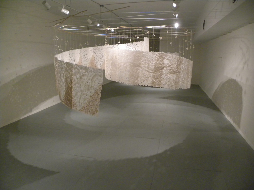 large handmade paper suspended from the ceiling in two spiraling paths that meet in the center