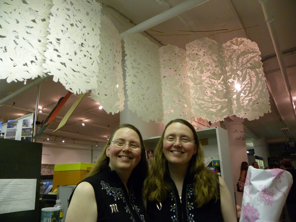 artists with installation of handmade paper suspended from the ceiling in a graceful S curve