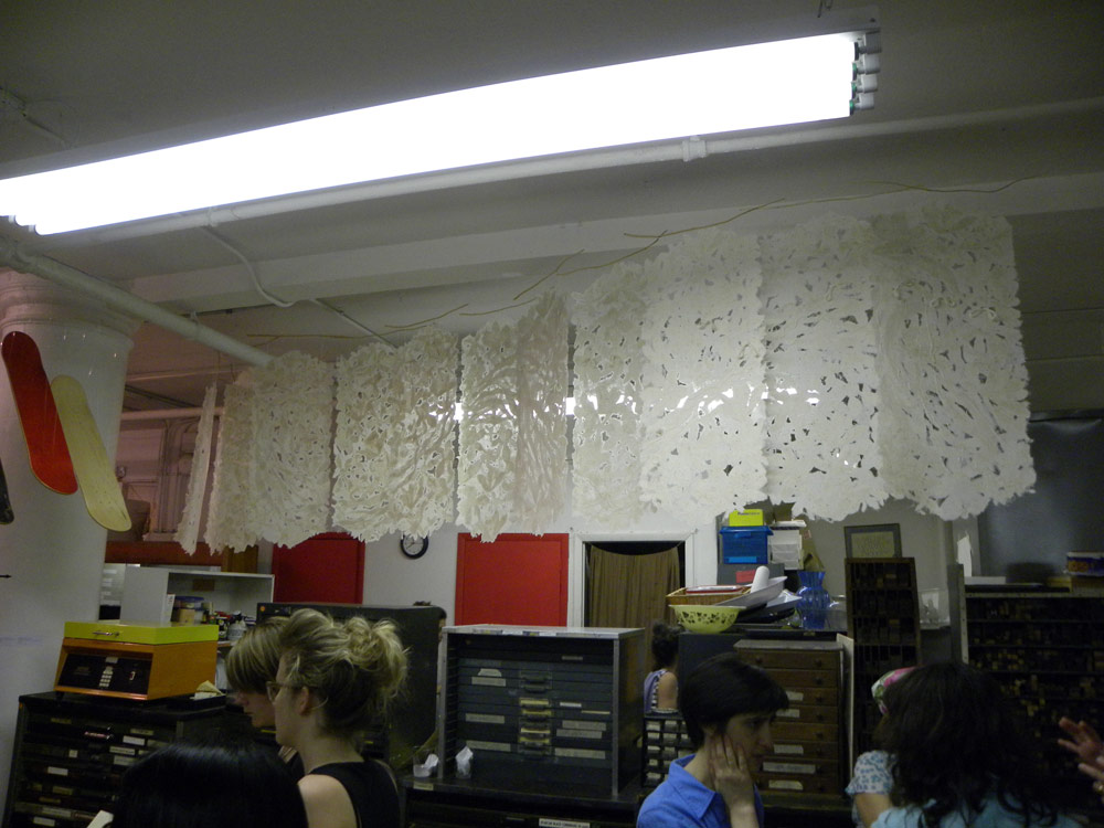 handmade paper suspended from the ceiling in a graceful S curve