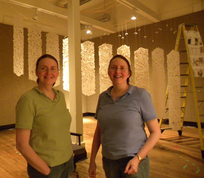 artists with their large handmade paper suspended from the ceiling in an ascending graceful curve