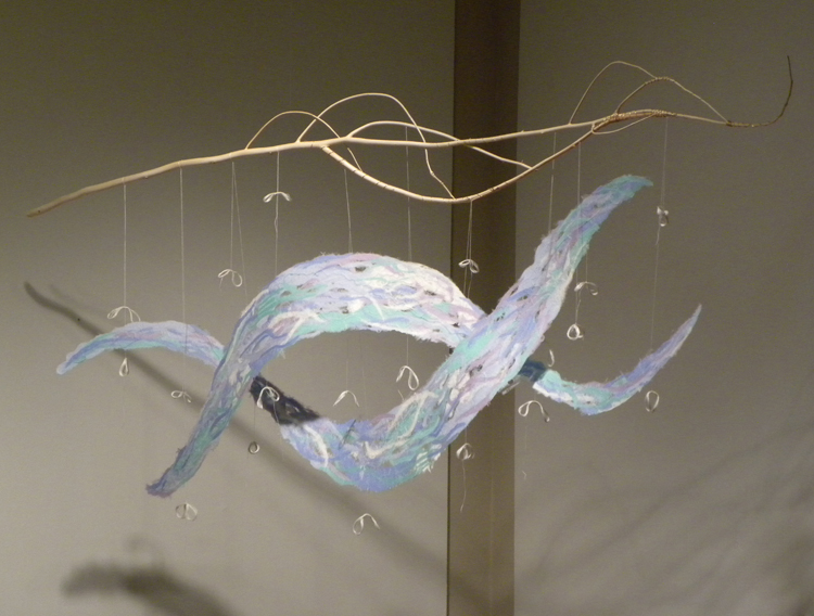 handmade paper wave shapes suspended from a branch